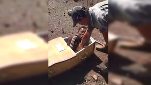 A white South African farmer forced a black man to get into a coffin. Screen grab of video, below.