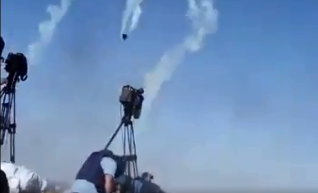 Journalists shield themselves from tear gas released by Israeli drones.