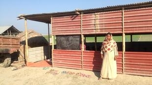 Jamila outside of her temporary school - a hut situated behind her house.