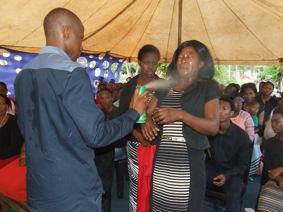 Une femme reçoit de l'insecticide dans les yeux. Photo publiée sur la page Facebook de l'église du pasteur.