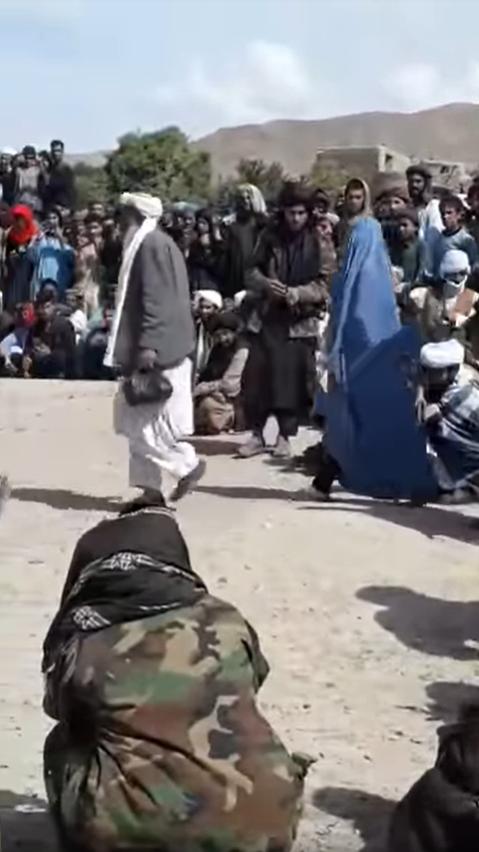 """La victime est amené au centre d'un regroupement d'hommes, par l'un des """"juges"""" taliban."""