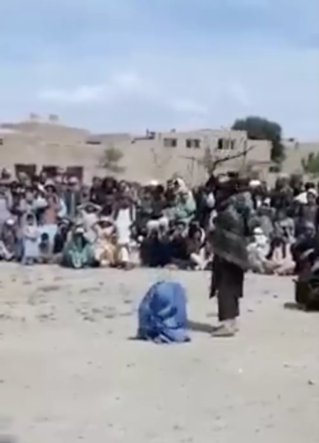 Two members of the Taliban deliver 40 lashes to their victim, a woman who is kneeling, as a crowd looks on.