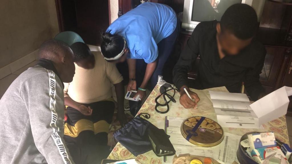 Des médecins et infirmiers visitent la maison d'un patient ayant eu besoin d'analyses après une attaque, il a aussi du diabète et de l'hypertension. Les visages ont été floutés afin de protéger l'identité des professionnels de santé.