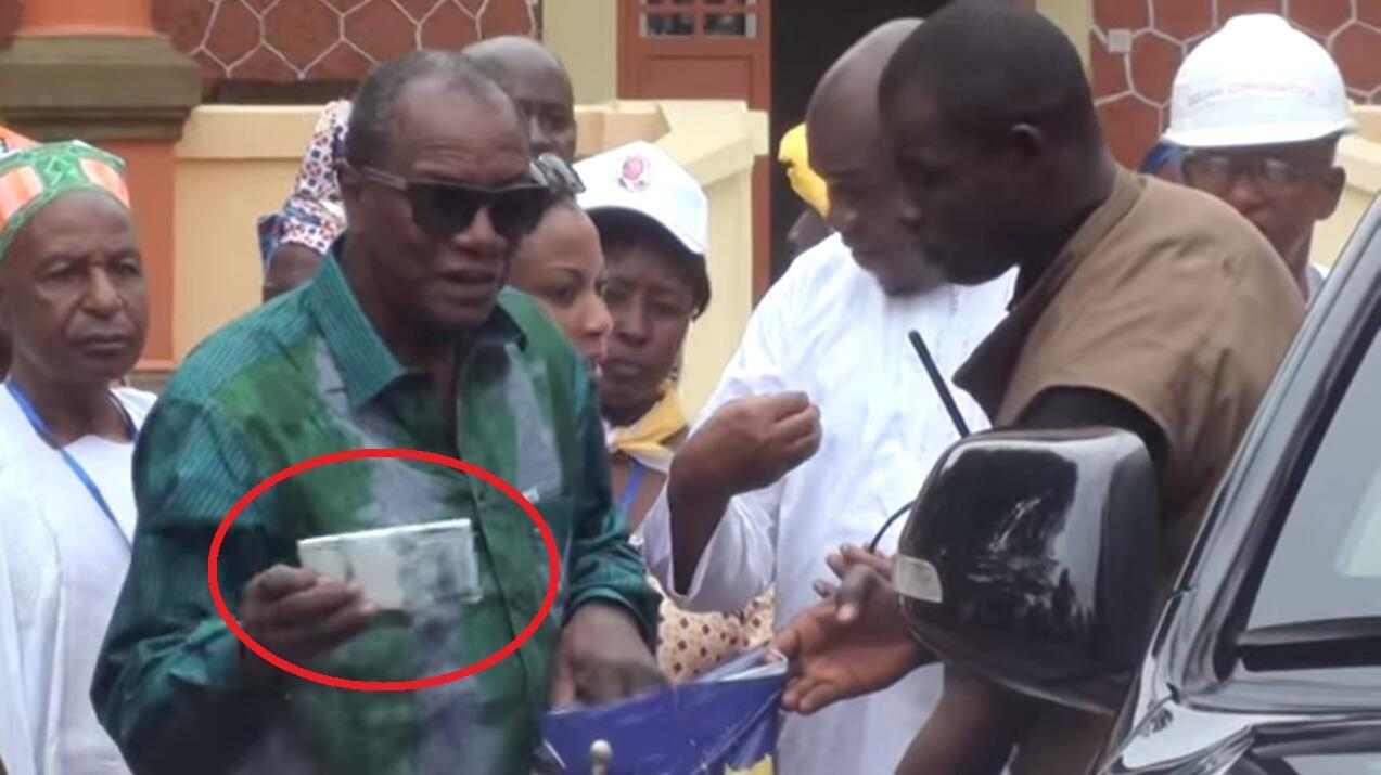 Le président Alpha Condé remet de l'argent pour une fanfare venue jouer en son honneur. Capture d'écran vidéo ci-dessous.