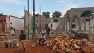Des assaillants viennent de détruire une partie des murs de la mosquée Lakouanga lundi à Bangui. L'un d'entre eux a une hache à la main.