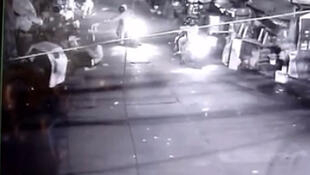 A screenshot from CCTV footage showing unidentified gunmen shooting at a crowd.