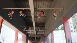 Des membres du gouvernement affublés de corps de cafards suspendus à un pont d'un quartier de Hong Kong.