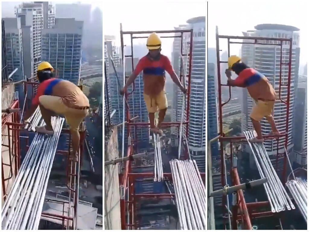 A construction workers installing scaffolding on a very tall building - without a safety harness.