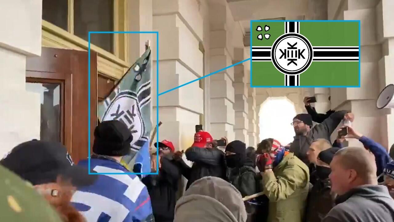 A rioter carries a flag for the imaginary nation of Kekistan as he tries to enter the Capitol on January 6, 2021. In the upper left corner, you can see the original flag for reference.
