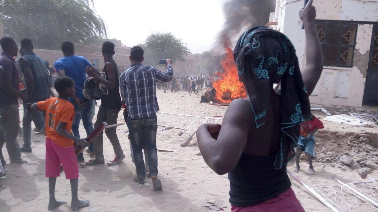 Des manifestants sont réunis devant un bar de Tombouctou, des meubles sont brûlés devant l'entrée. Image publiée sur Facebook.
