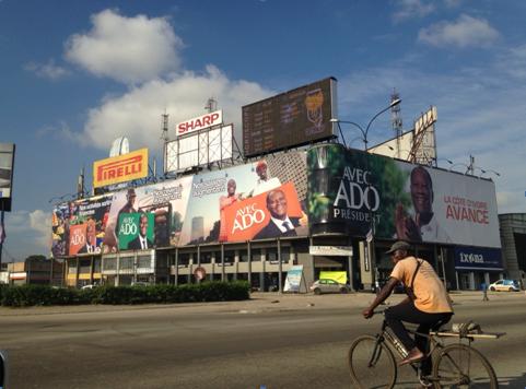 """Plusieurs affcihes pour """"ADO"""" (Alassane Dramane Outtara) au carrefour de Marcory et Treichville à Abidjan. Photo : Guillaume Guguen."""