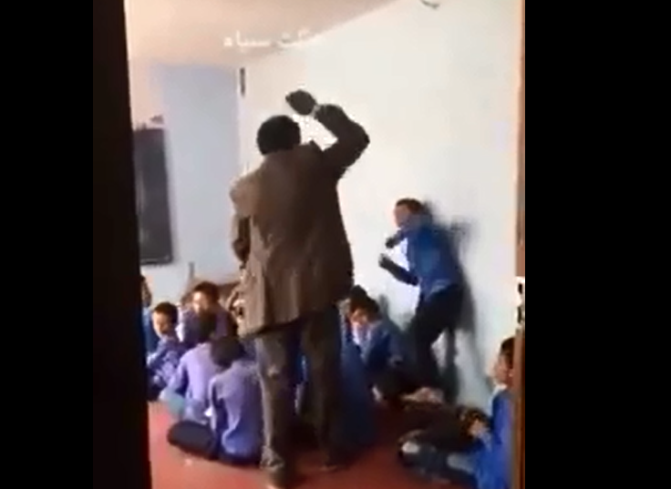 Screen grab of video showing an Afghan teacher beating a schoolchild with prayer beads