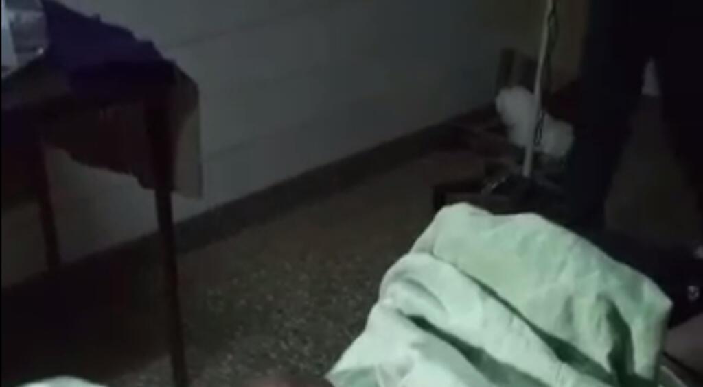 Capture d'écran de la partie supérieure de la vidéo, filmée à la verticale, qui montre une partie de la salle d'opération, et le drap vert recouvrant le haut du corps de la patiente. Derrière, un personnel de l'hôpital contourner la table d'opération.