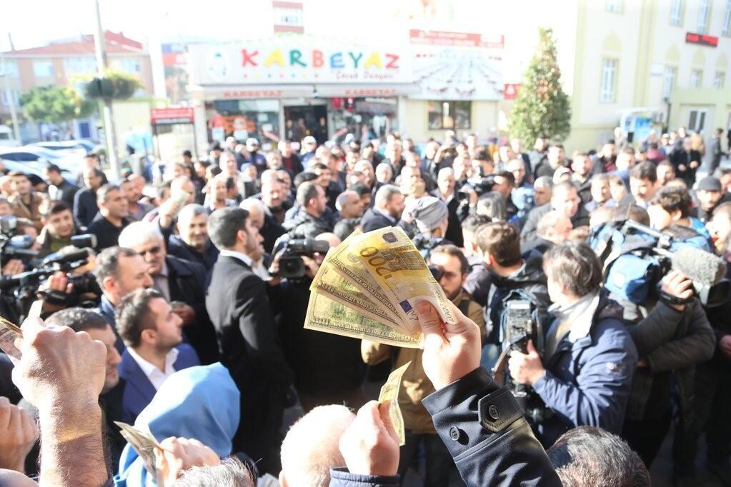 Un homme brandit des dollars et des euros devant un bureau de change à Istanbul. Photo : Nadir, @Zikirci sur Twitter