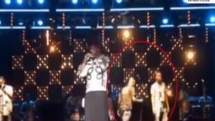 Several people have created videos suggesting conspiracy theories around the death of Congolese musician Papa Wemba. This video highlights a stage assistant (circled in red on this photo), who some claim brought a poisoned microphone on stage.
