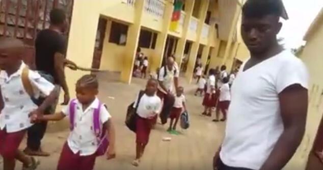 A screen capture from a video showing children fleeing a school.