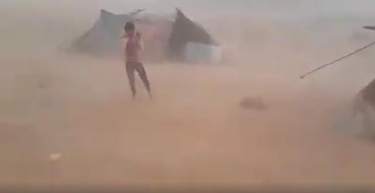 Capture d'écran d'une vidéo montrant une tempête de sable balayer un campement de migrants Syriens coincés à la frontière entre le Maroc et l'Algérie.
