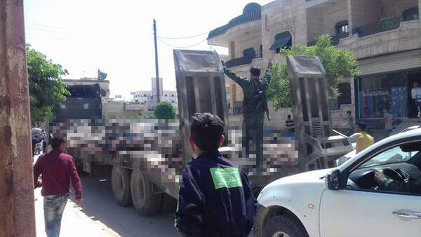 Un combattant kurde debout sur un camion-remorque avec à ses pieds plusieurs dizaines de cadavres est acclamé par la population.