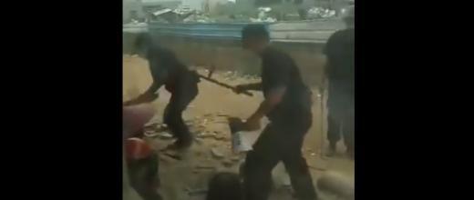 Des policiers chinois frappant une femme durant l'évacuation. Image issue de la vidéo ci-dessous.