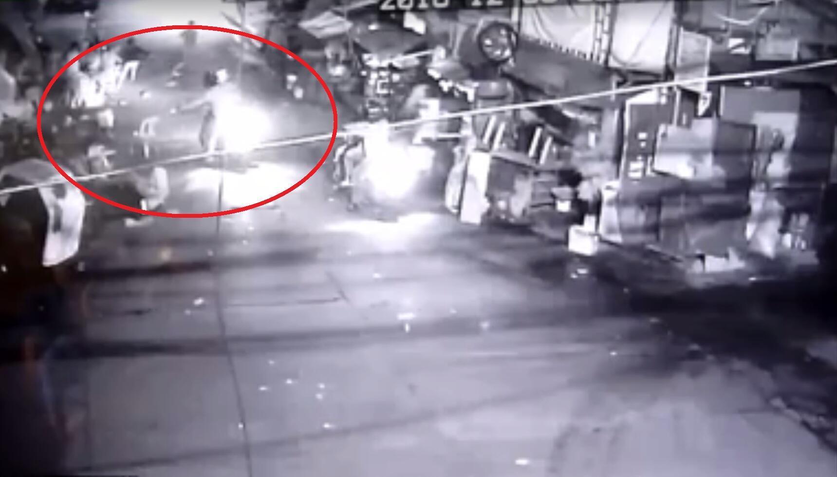 Sur cette image de vidéo surveillance, un homme en scooter tire avec un pistolet sur des personnes dans un quartier de Makati aux Philippines.