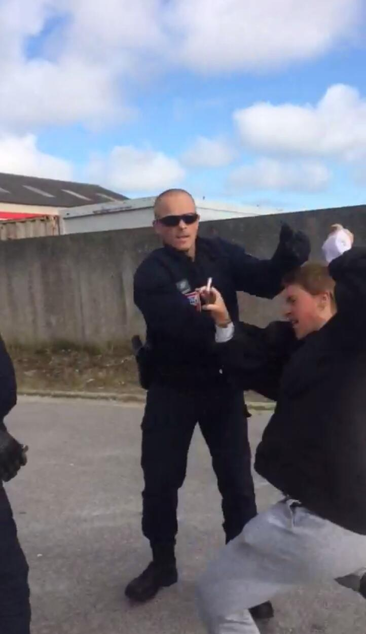 """Screen grab of a video sent by """"L'Auberge des migrants"""" showing a riot police officer shoving a volunteer who had been filming the police."""