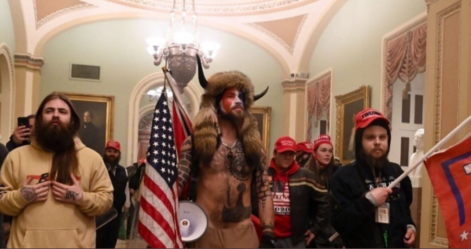 "Jake Angeli, who goes by ""Q Shaman,"" carries an American flag and a megaphone in the entrance to the Capitol building in Washington."