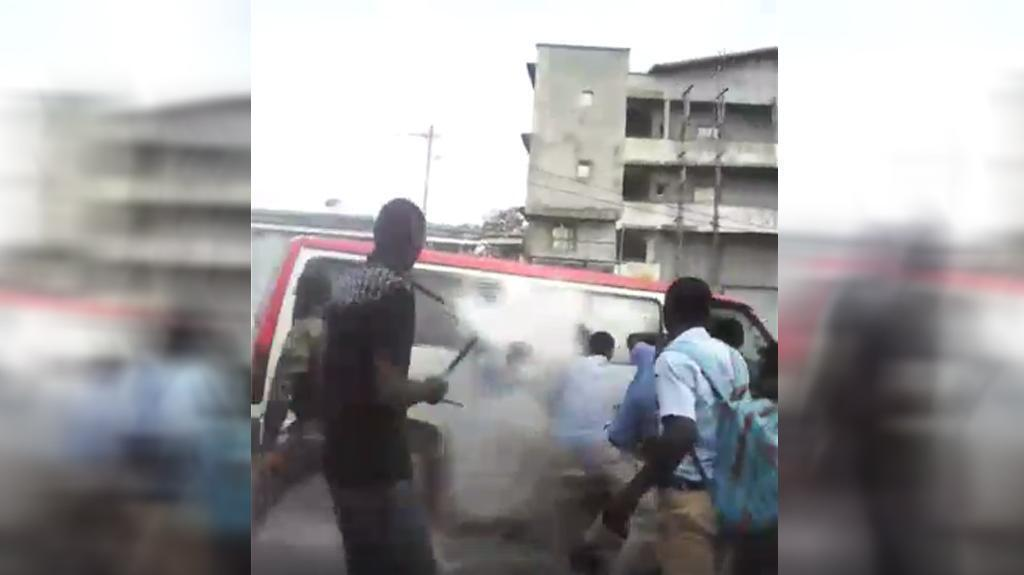 Screen capture from a video filmed on Wednesday November 8 in Libreville, which shows a police officer throwing a tear gas canister inside a school bus. Source: Facebook.