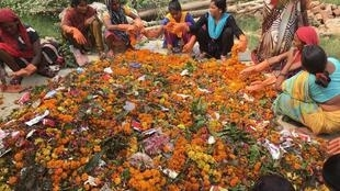 Women sort flowers discarded from temples.