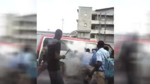 Capture d'écran d'une vidéo tournée mercredi 8 novembre à Libreville, et qui montre un gendarme jeter une bombe lacrymogène à l'intérieur d'un minibus. Source : Facebook.