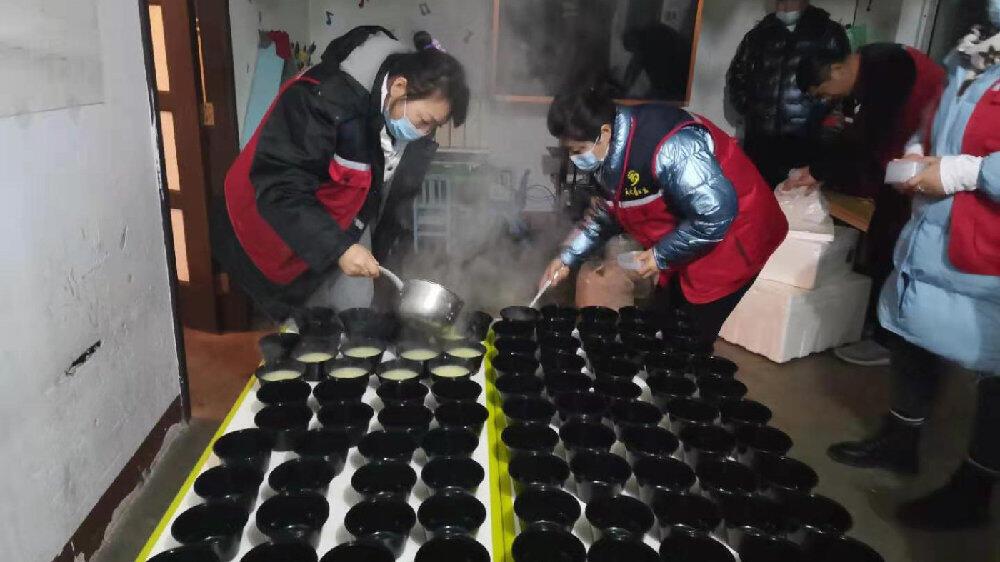Des volontaires du Qixia Sky Blue Charity Group distribuent du riz aux équipes de sauvetage sur le site de la mine d'Hushan. Image via Weibo.