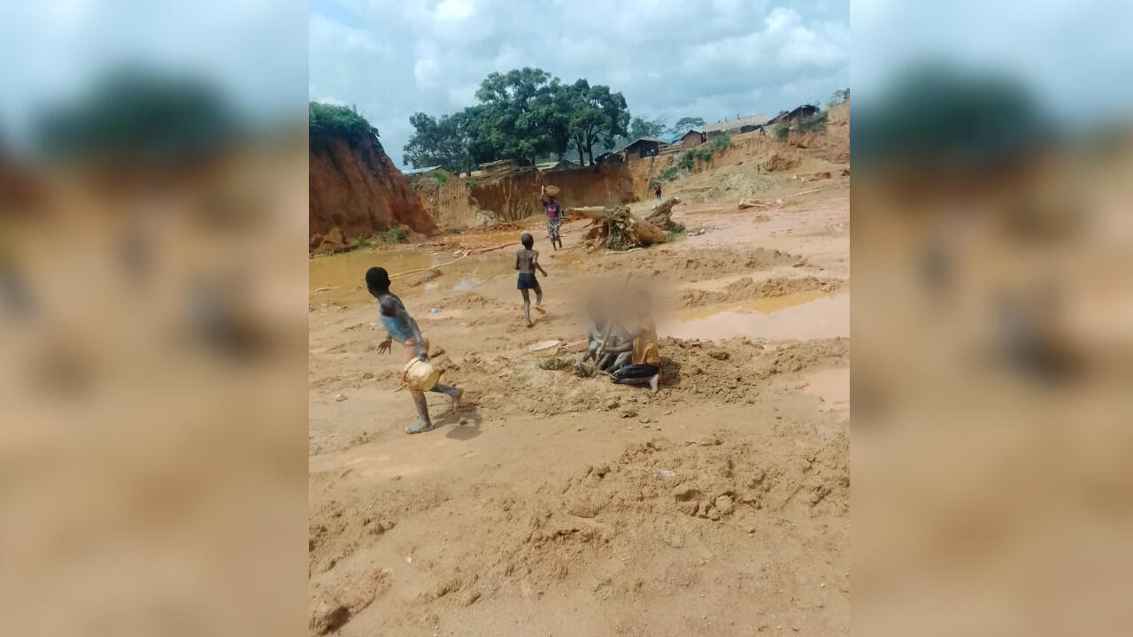 Des enfants dans la mine de Kambélé assis près d'un étang.