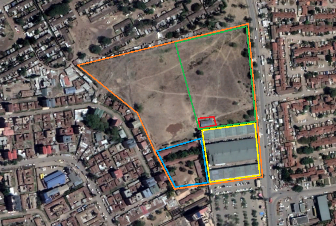 The Martin Luther Primary School sits on a large piece of land (marked in orange). The schools buildings (in blue) are in one corner of the property and the remaining empty land is used as a playground and field by students. The demolished building is marked in red, within a zone that has been disputed for decades (in green). The buildings in yellow are private businesses that have been built on land that was previously used by the school.