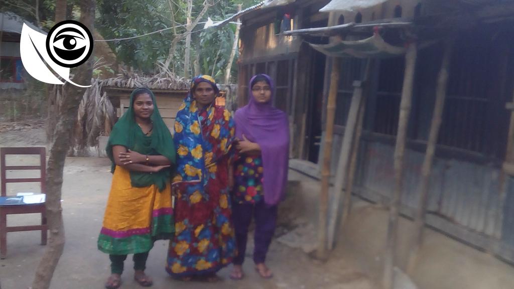 Marjina et des voisines, devant sa maison et son panneau solaire, sur le toit. Photo : Sharmishtha Roy/Adams.