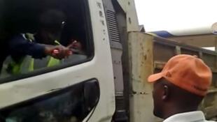 Un policier, installé sur le siège conducteur d'un camion de marchandise, refuse de laisser le chauffeur reprendre son véhicule.