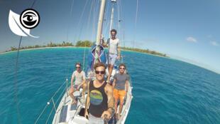 Les quatre membres de l'Eco Sailing Project sur leur voilier équipé de panneaux solaires et d'une éolienne.