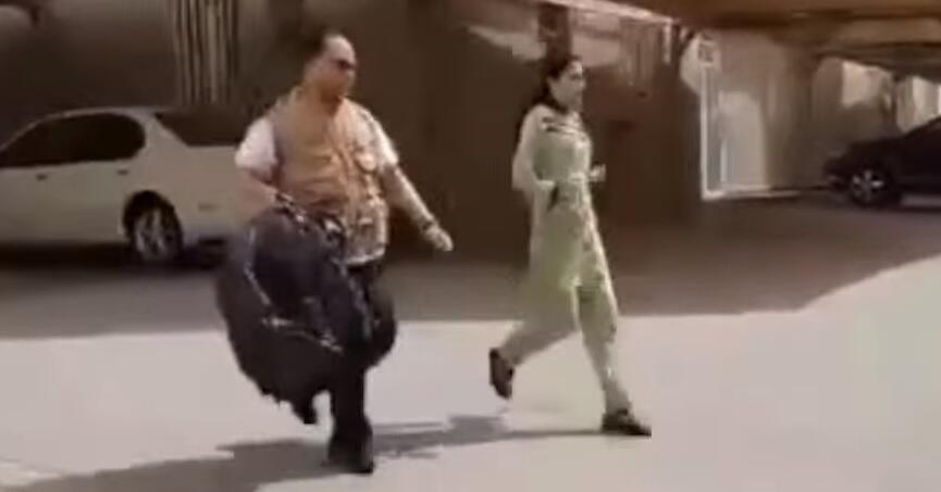 Capture d'écran d'une vidéo qui montre un membre du personnel de l'ambassade accompagnant une employée de maison qui vient de s'enfuir de chez son employeur.