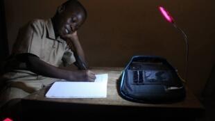 Un enfant ivoirien utilise le cartable solaire inventé par notre Observateur pour étudier à la nuit tombée. Photo Solarpak.