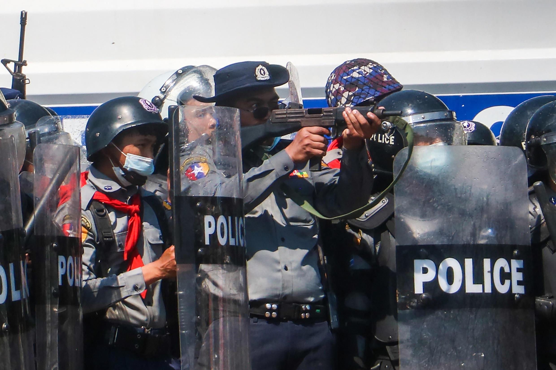 Un officier de police vise avec son arme à Naypyidaw le 9 février 2021, vers 13h.