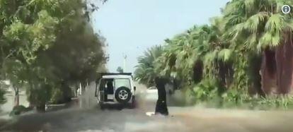Capture d'écran d'une vidéo postée sur Twitter, sur laquelle on voit une personne portant l'abaya traditionnelle des Saoudiennes surfer, tractée par une voiture, dans les rues de Jeddahh inondées.