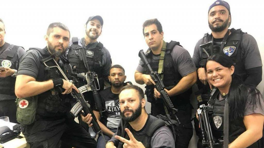 Brazilian police officers pose with a drug trafficker nicknamed Rogerio 157 shortly after he was arrested in Rio de Janeiro on Wednesday, December 6. (Photo posted on social media)