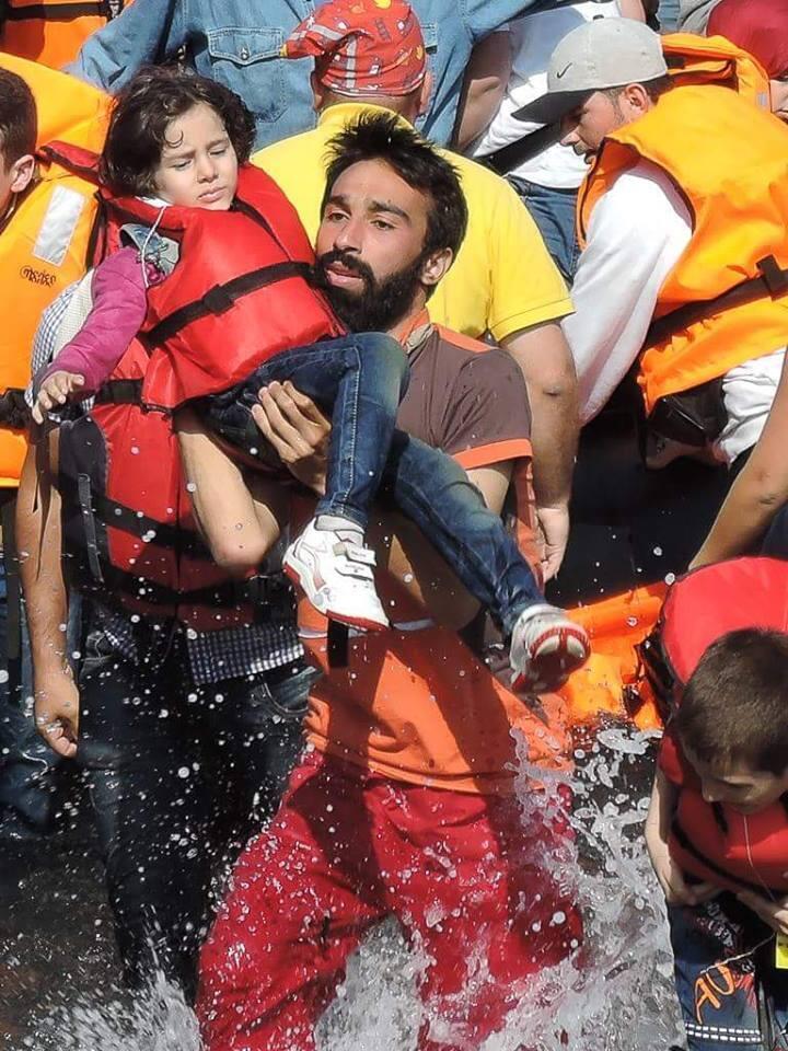 Kinan Kadoni porte une enfant hors de l'embarcation. Ile de Lesbos, Grèce. Photo: Rutget Verhaegen
