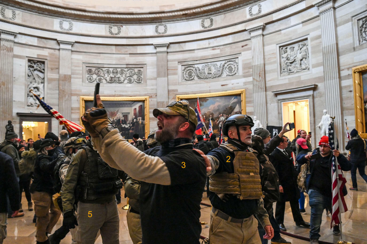 In an image by photographer Saul Loeb widely shared on social media, militia members take pictures in the atrium of the Capitol.