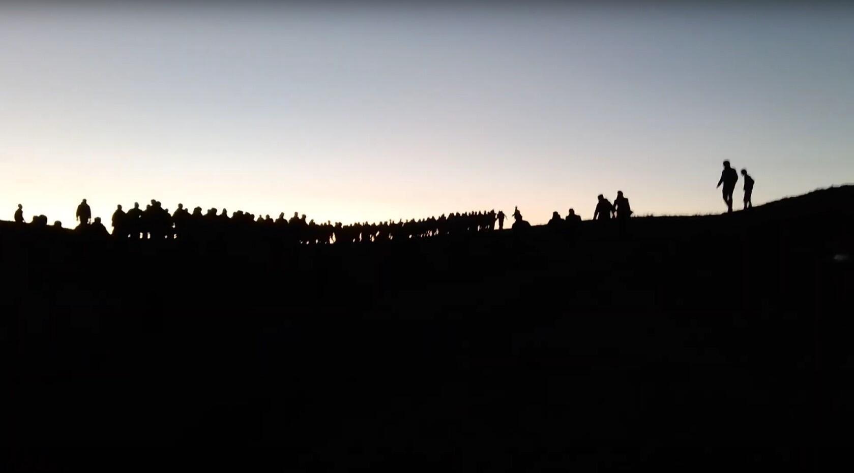 این تصویر برگرفته از ویدئویی که در تاریخ 12 ماه مه منتشر شده است، گروهی متشکل از دهها مهاجر را نشان میدهد که به سمت مرز ترکیه در حوالی روستای کارکوش، در دو کیلومتری محل فیلمبرداری اولیه، در حال پیشروی هستند.