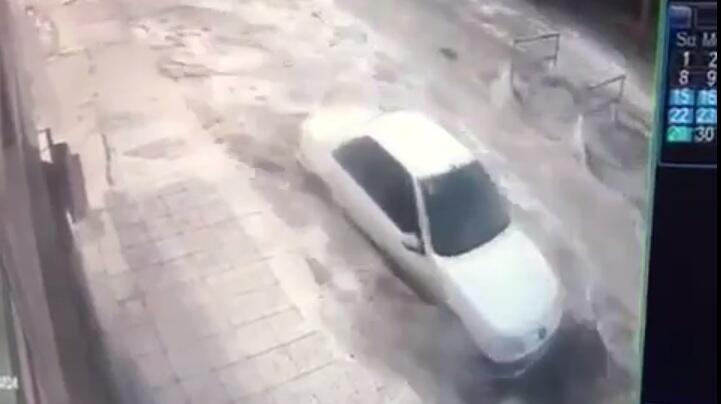 Une voiture et un motard échappent de justesse à la montée des eaux à Dayyar, alors qu'une tempête frappe la ville.