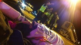 """Des activistes britanniques (visibles au premier plan) ont réussi à empêcher un avion de décoller la semaine dernière, malgré l'arrivée de policiers. Photo publiée sur la page Facebook """"Stop Charter Flights - End Deportations""""."""