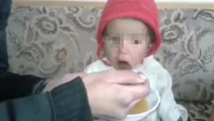 Capture d'écran d'une vidéo ci-dessous, dans laquelle une mère explique qu'elle doit nourri son bébé avec de l'eau et un peu de confiture pour lui redonner des forces.