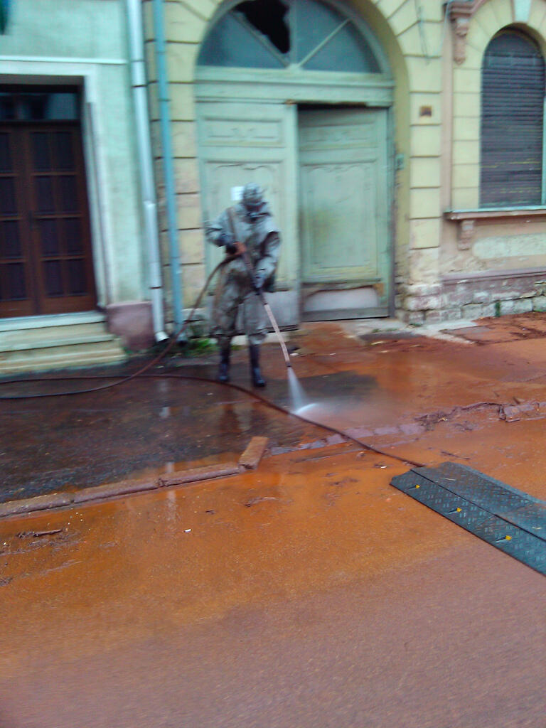 Soldier in full protection gear cleaning the streets of Kolontar on October 5.