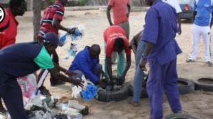 Des habitants de Keur Moussa remplissent un pneu de sacs plastiques pour créer un banc. Photo 3000 Ecomen.