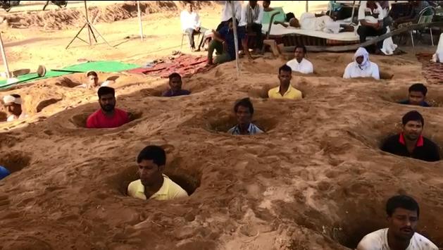 صورة ملتقطة من فيديو يظهر فيه مزارعون يدفنون أنفسهم داخل حفر احتجاجا على مشروع سكني