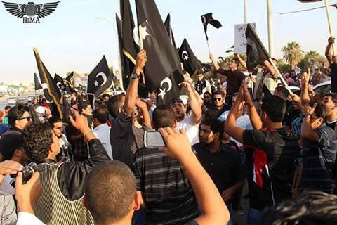 المدعوون يرفعون العلم الأسود المرسوم عليه نجمة وهلال الذي اختاره إدريس السنوسي عند إعلان إنشاء إمارة البرقة عام 1951.